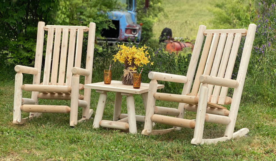 outdoor seating crafted with log furniture - two rocking chairs and a table between them